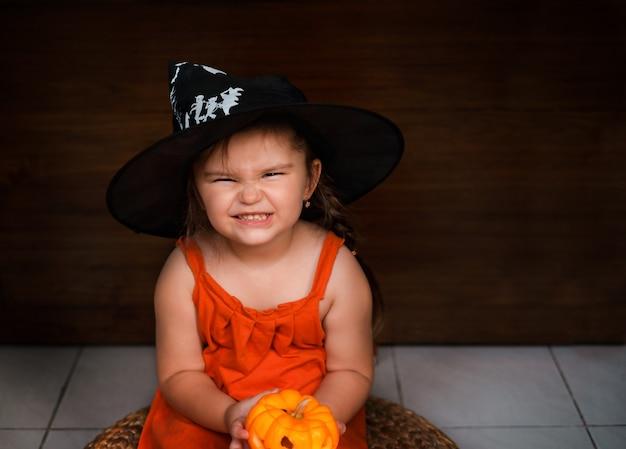 Ragazza del bambino che tiene la decorazione di halloween jack-o-lantern sulle piccole mani su un fondo di legno