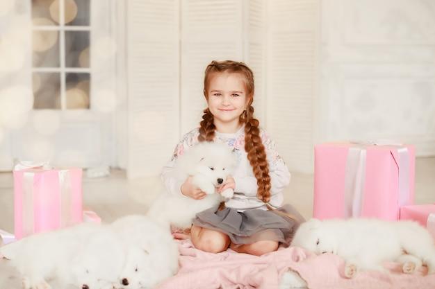 La ragazza del bambino sta tenendo il cucciolo sulle sue mani vicino al rosa i contenitori di regalo
