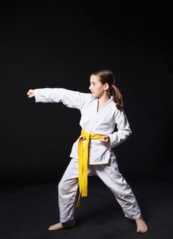 Ragazza del bambino in tuta di karate con posizione spettacolo cintura gialla