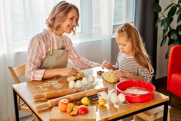 Ragazza del bambino impasta con la mamma in cucina, andando a cuocere deliziosi biscotti. famiglia a casa nel fine settimana, la madre insegna alla bambina a cucinare