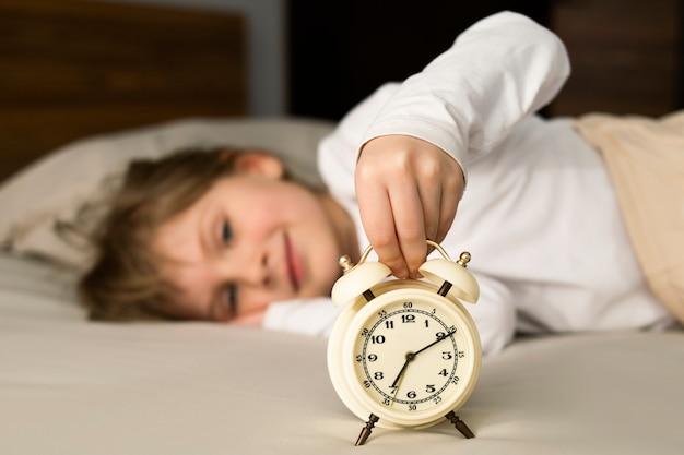 La bambina è sdraiata a letto la mattina e sorride, spegne la sveglia. buon umore dopo un sonno salutare.