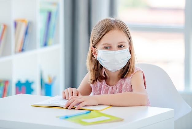 Ragazza del bambino nella mascherina medica studiando a scuola