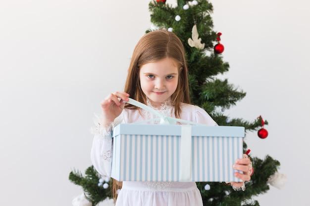 La ragazza del bambino apre il contenitore di regalo sopra l'albero di natale