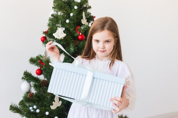 La ragazza del bambino apre il contenitore di regalo vicino all'albero di natale