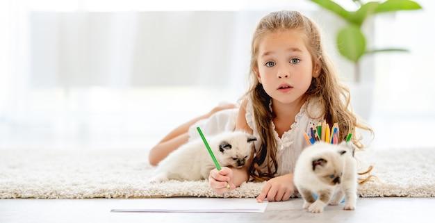 Ragazza bambino dipinto con gattini ragdoll sul pavimento. piccola persona di sesso femminile che disegna con matite colorate e gattini vicino a lei a casa