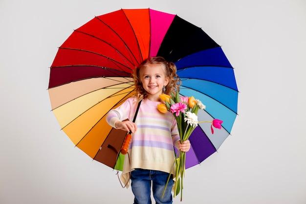 Ragazza del bambino in stivali di gomma che tengono un ombrello multicolore