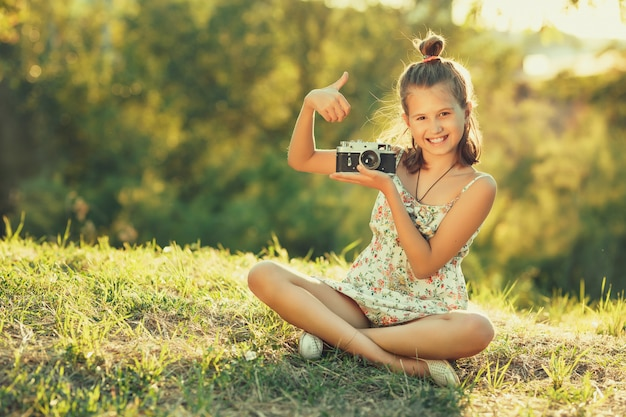 Ragazza del bambino che si siede sull'erba. ha tra le mani una vecchia macchina fotografica e mostra i gesti
