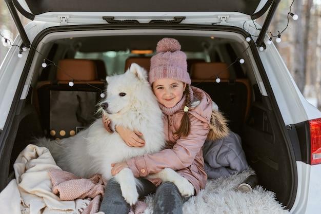 Bambina seduta nel bagagliaio dell'auto con il suo animale domestico, un cane bianco samoiedo
