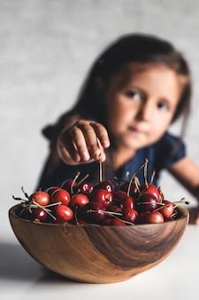 Ragazza del bambino che si siede sul davanzale della finestra a casa e mangiare ciliegie dolci. frutta estiva, cibo vitaminico stagionale sano.