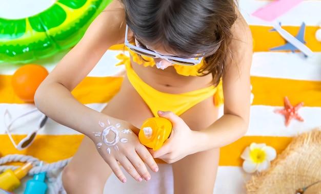 Una bambina spalma la protezione solare sulla sua pelle. messa a fuoco selettiva. ragazzo.