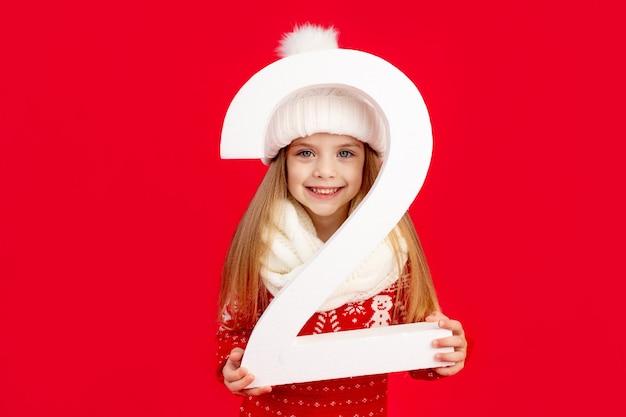 Una bambina con un cappello invernale e un maglione con un grande numero due su uno sfondo rosso monocromatico isolato si rallegra e sorride, il concetto di capodanno e natale, spazio per il testo