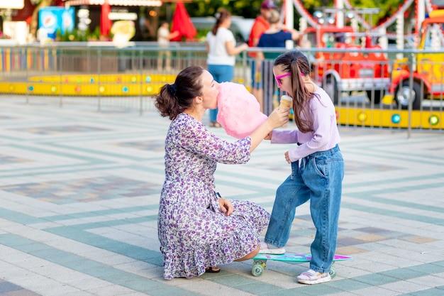 Una bambina con sua madre in un parco divertimenti in estate mangia zucchero filato e gelato vicino alle giostre, scherzando e ridendo, il concetto di fine settimana in famiglia e vacanze scolastiche