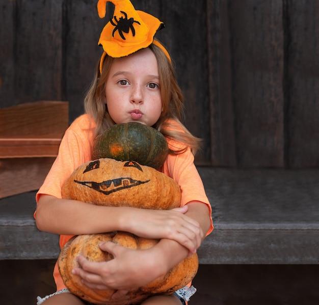 Ragazza del bambino con le zucche nelle decorazioni di halloween su un fondo di legno