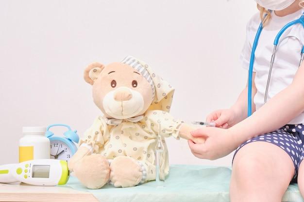 Un bambino fa un'iniezione a un orso giocattolo, il dottore del concetto di vaccinazione gioca a un orsacchiotto