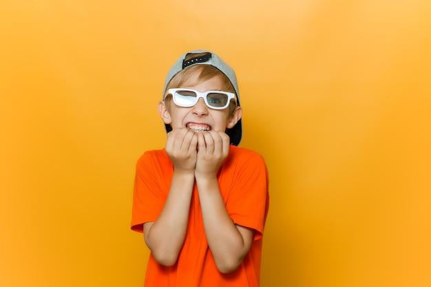 Un bambino con gli occhiali per guardare un film si mangia le unghie per paura