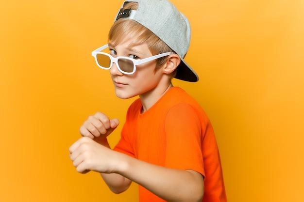 Un bambino con gli occhiali per guardare film ha stretto i pugni e guarda di traverso la telecamera