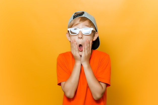 Un bambino con gli occhiali per guardare film ha aperto la bocca per la sorpresa e si è tenuto le guance con le mani