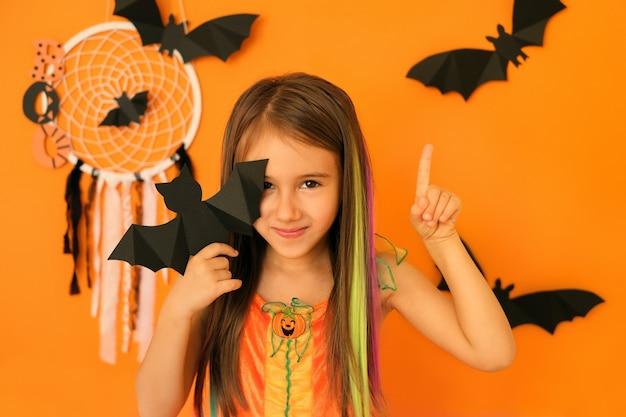 Il bambino il giorno di halloween mostra qualcosa sopra la sua testa che punta con il dito indice verso l'alto