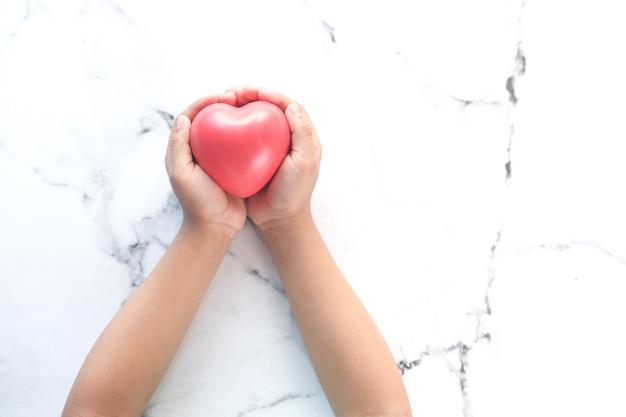 Mano del bambino che tiene cuore rosso su bianco