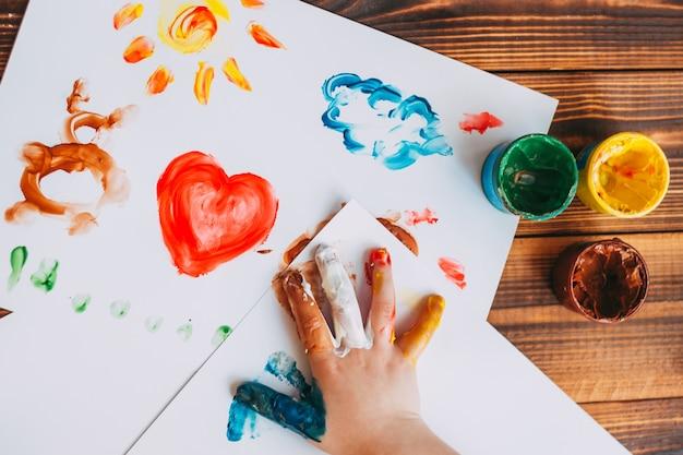 Bambino dipinto a mano mosaico colorato il bambino sta disegnando il palmo su fogli bianchi con vernici