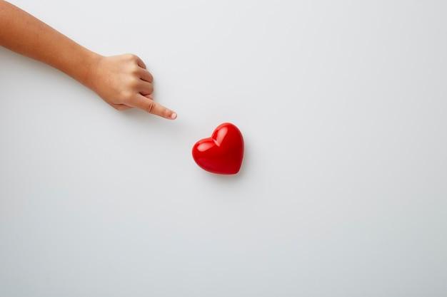 Mano del bambino che indica cuore rosso su priorità bassa bianca