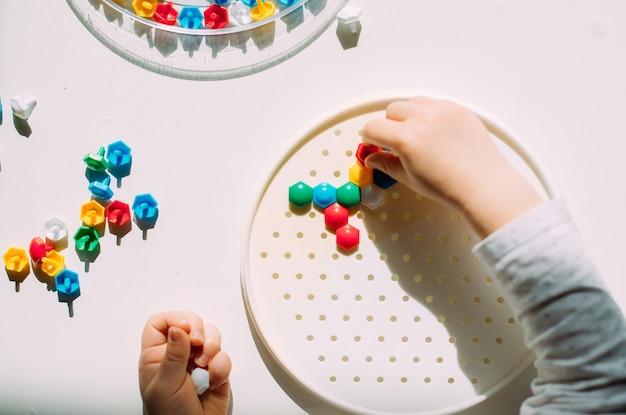 La mano del bambino infila il mosaico nella forma.