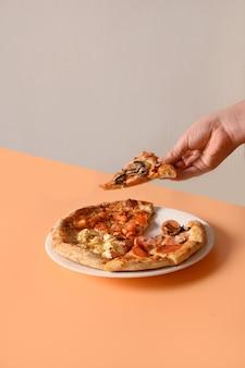 La mano del bambino prende il tipo della pizza italiana quattro con ingredienti differenti
