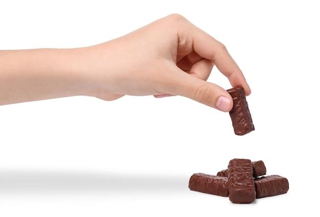 La mano del bambino prende la caramella di cioccolato, isolata su priorità bassa bianca. mano che tiene la caramella di cioccolato sul mucchio di caramelle.