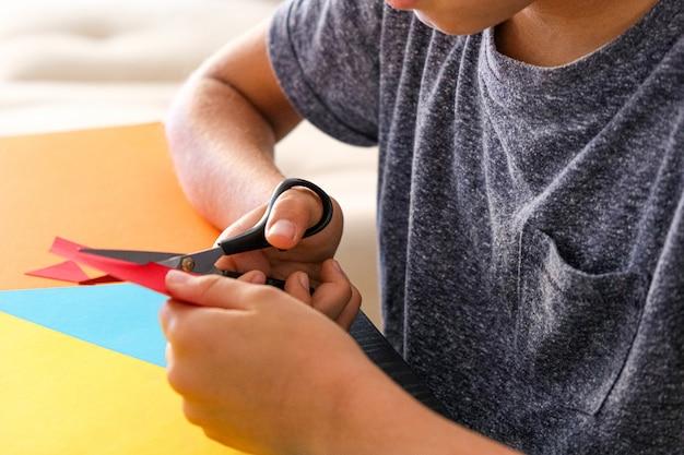 Mani del bambino che tagliano carta colorata con le forbici al tavolo