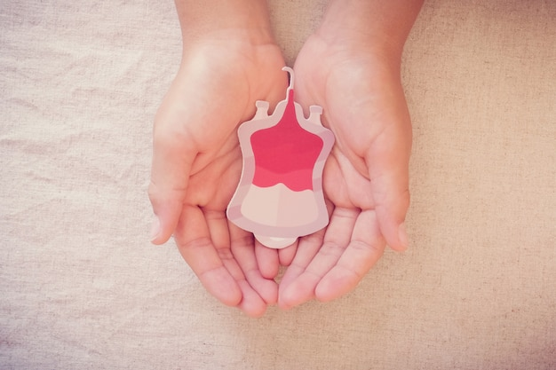 Mani del bambino che tengono la sacca di sangue di carta