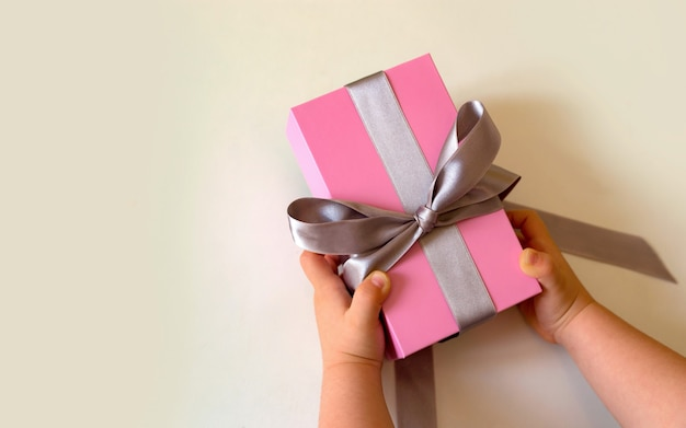 Mani del bambino che tengono confezione regalo rosa con fiocco d'argento