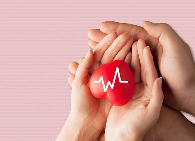 Mani del bambino che tengono il cuore rosso