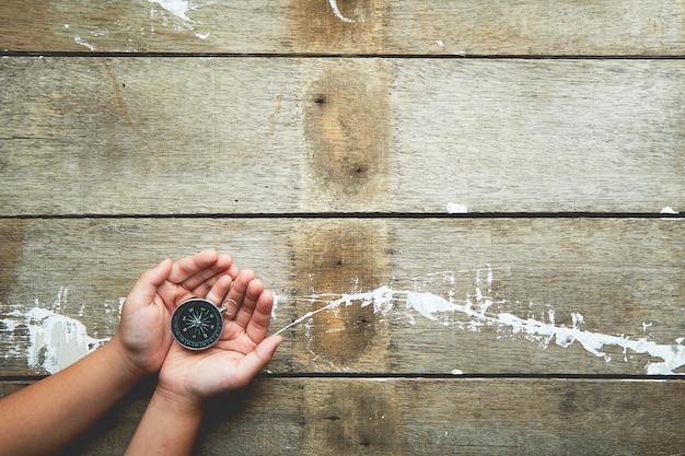 Bussola holiding delle mani del bambino su di legno