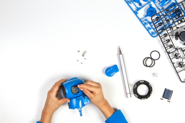 Mani del bambino che fanno un robot blu