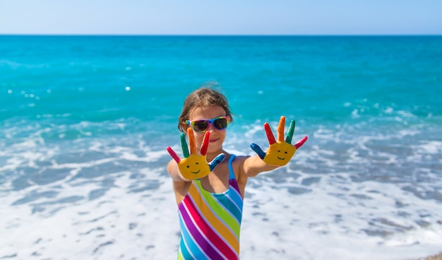 Mani di bambino dipinte con vernici sul mare. messa a fuoco selettiva. ragazzo.