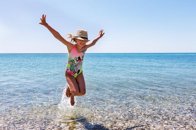 Il bambino salta felicemente tra le onde del mare sulla spiaggia in estate e guarda la telecamera