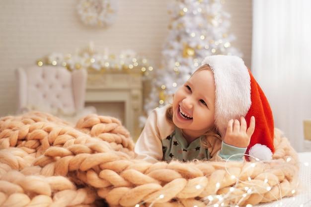 Bambino in un cappello su una coperta di lana di pecora naturale