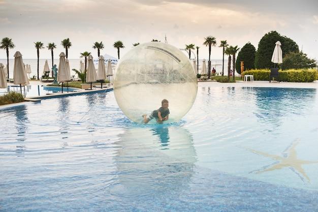 Il bambino si diverte all'interno di un grande pallone di plastica sull'acqua della piscina nella località estiva. ragazzino dentro la grande palla trasparente gonfiabile correre e divertirsi.