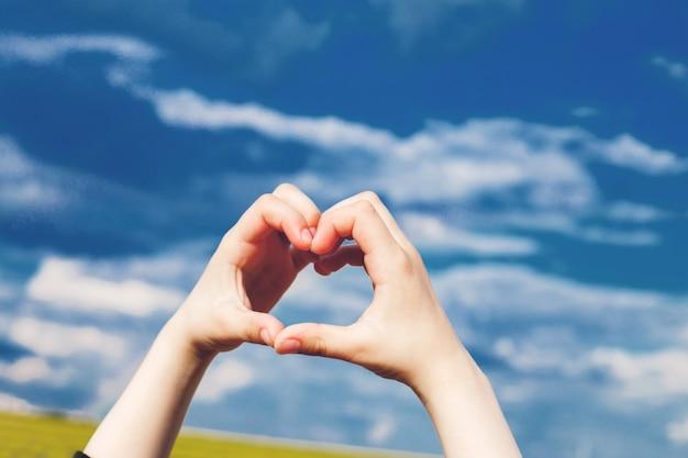 Cuore del bambino dalle mani su uno sfondo di cielo blu