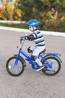Un bambino in un casco e protezione in un giro in bicicletta sulla natura in primavera