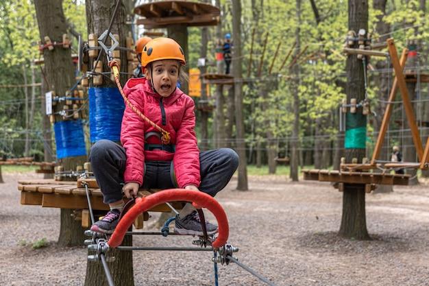 Un bambino con il casco e con l'attrezzatura sale le funivie nella foresta.