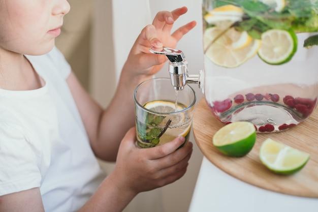 Il bambino stesso versa la limonata in un bicchiere rinfrescante bevanda estiva i bambini hanno preparato la loro limonata...