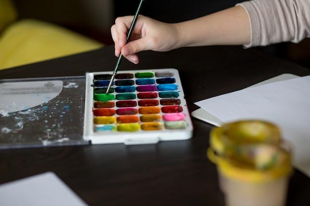Spazzola e pittura della tenuta del bambino sul libro bianco