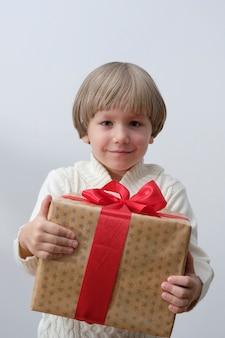 Contenitore di regalo di natale della holding del bambino in mano. ragazzo isolato su sfondo bianco. anno nuovo e concetto di natale.