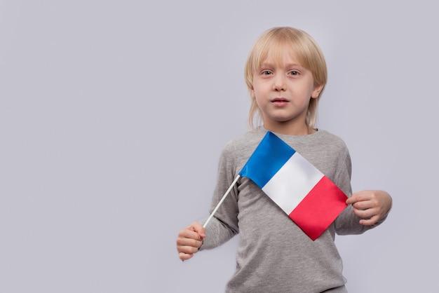Bambino che tiene la bandiera della francia
