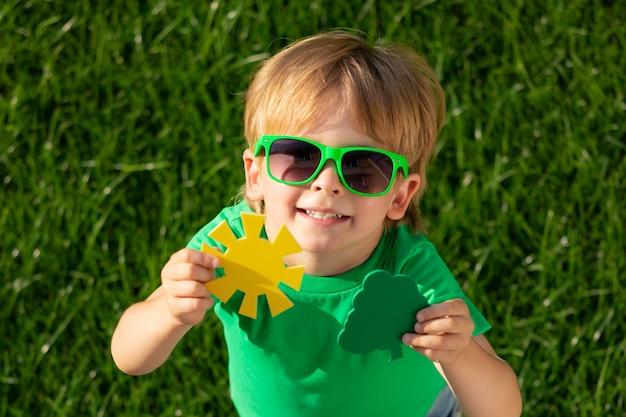 Bambino che tiene albero verde e sole nelle mani