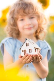 Bambino che tiene la casa in mano sullo sfondo del fiore di primavera. concetto immobiliare