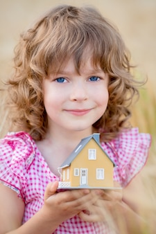Bambino che tiene casa nelle mani su sfondo giallo autunnale. concetto immobiliare