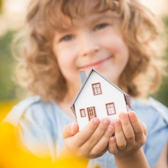 Bambino che tiene casa nelle mani sullo sfondo del campo di girasoli. concetto immobiliare