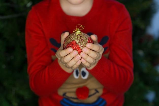 Bambino che tiene una palla della decorazione di natale